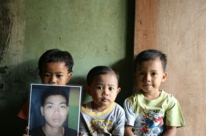 Relatives hold a picture of Yusli, killed in police custody